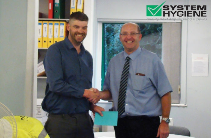 Photograph of phil barrett purchasing manager being presented a gift from general manager paul stebbings